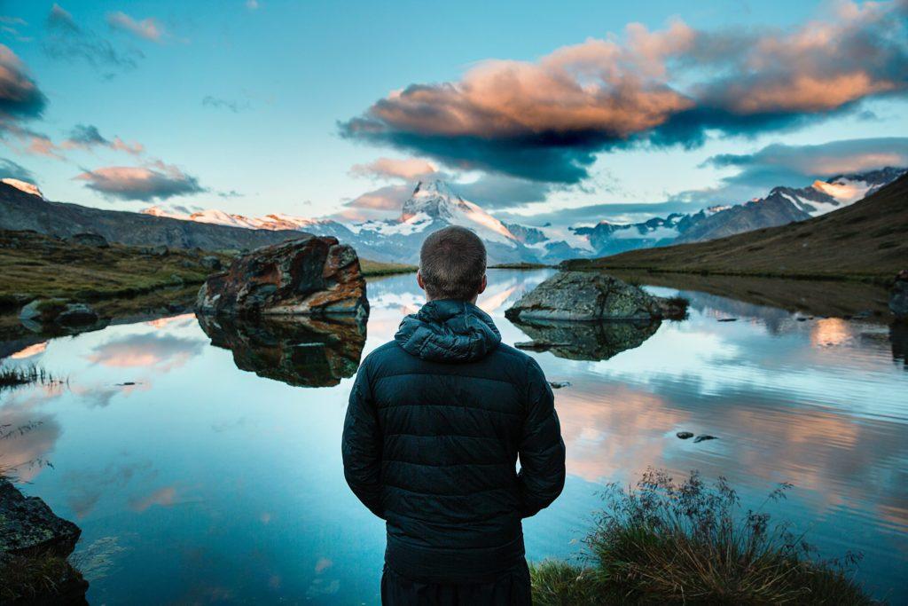 Мужчина размышляет в горах как измениться к лучшему